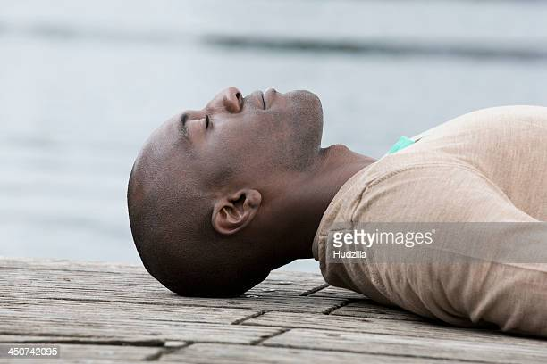 Man napping on decking by lake