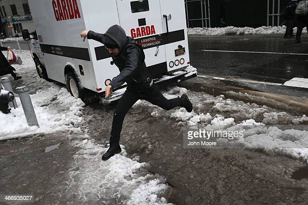 A man navigates a slushy intersection at Broadway and 14th Street at Union Square on February 5 2014 in New York City United States New Yorkers like...