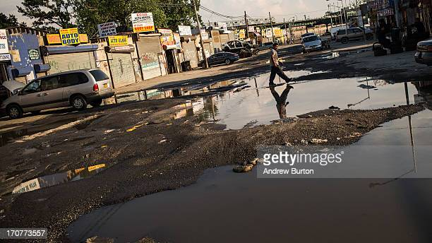 A man navigates the flooded streets on June 17 2013 in the Willet's Point neighborhood of the Queens borough of New York City The Willet's Point...