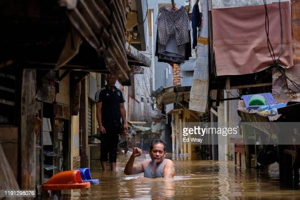Man navigates through his flooded neighborhood on January 2, 2020 in Jakarta, Indonesia. Flooding caused by heavy rain left at least 17 people dead...