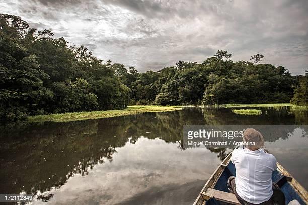 man navigating on amazon river, brazil. - río amazonas fotografías e imágenes de stock