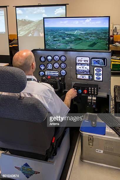 Man navigating virtual airplane in amateur flight simulator