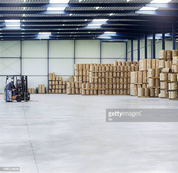 Mann in der Nähe in der Lagerhalle mit Gabelstapler StorageBarrels