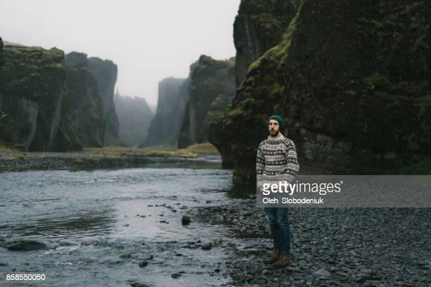 Man in de buurt van de rivier in Fjaðrárgljúfur canyon