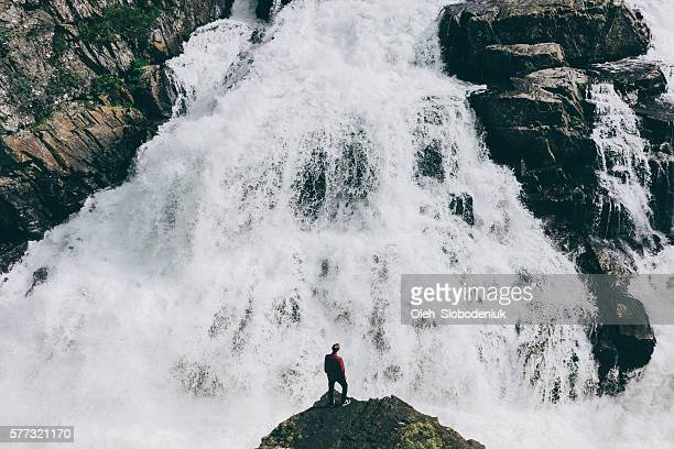 man near the waterfall - rivier stockfoto's en -beelden