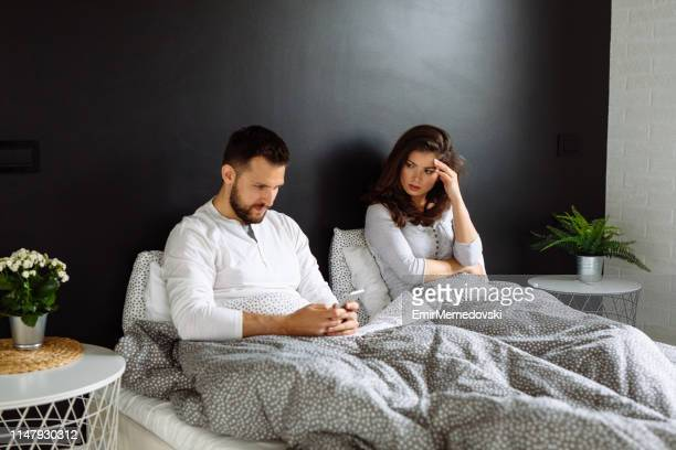 man neglecting his girlfriend and using his mobile phone in bed - cheating wife stock pictures, royalty-free photos & images