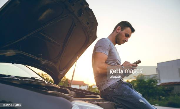 man next to a broken down car - broken down car stock pictures, royalty-free photos & images