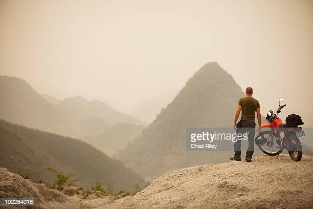 Man next to motorcycle viewing mountains