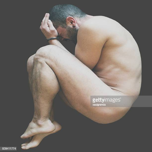 Man nude in a fetal position, black background