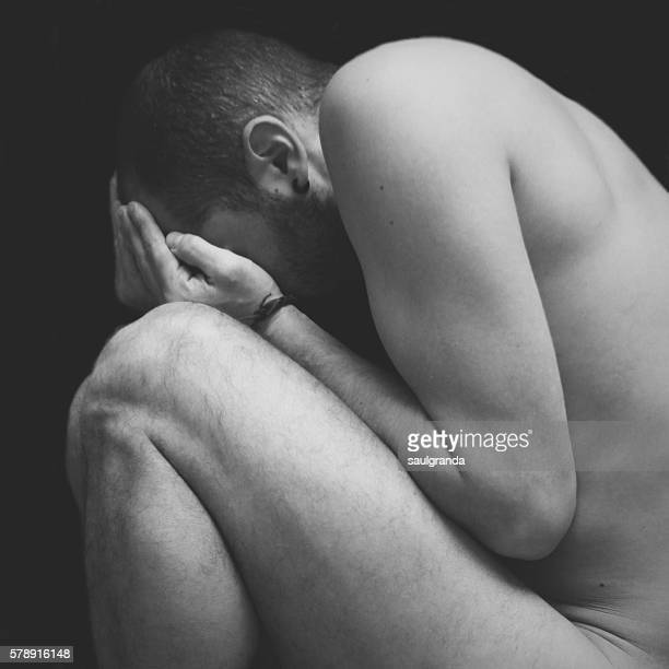 Man nude in a fetal position