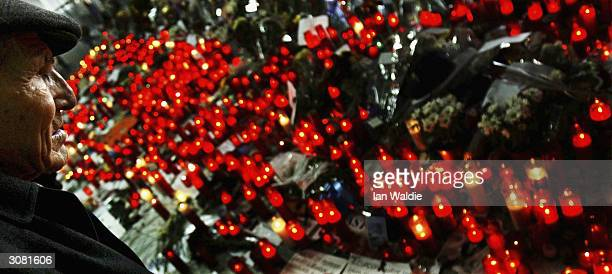 A man observes a minutes silence near a mass of red candles at Atocha train station as a memorial for those killed in the terrorist bombings March 13...