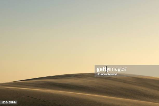 man observes sunset from the top of the dune - maranhao state stock pictures, royalty-free photos & images