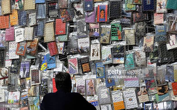 A man observes the covers of the books of the Tower of Babel a creation made by Argentine artist Marta Minujin with thousands of books in languages...