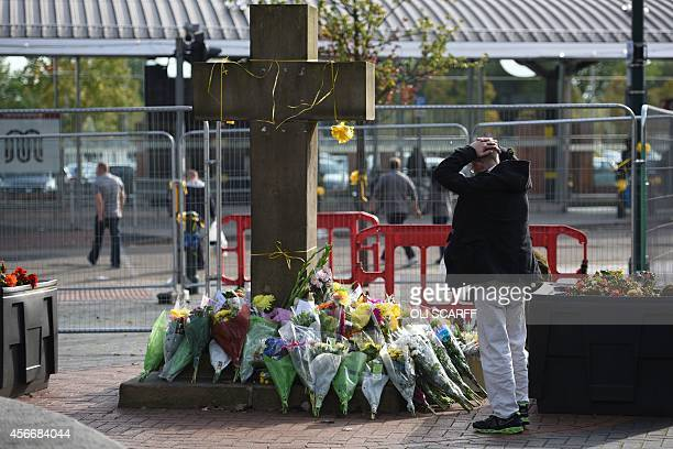 A man observes the floral tributes at the base of the Eccles Cross for murdered aid worker Alan Henning in Eccles north west England on October 5...