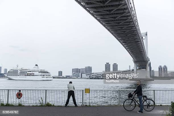 A man observes the passage of a cruise ship under the massive Rainbow Bridge Tokyo Japan The Rainbow Bridge is a suspension bridge crossing northern...