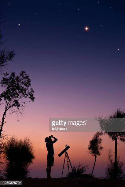 a man observing the night sky - telescope stock pictures, royalty-free photos & images
