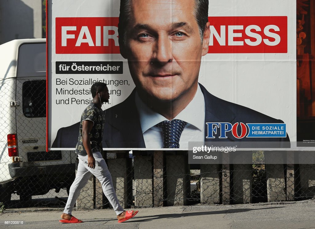 A man of African origin walks past an election campaign billboard that shows Heinz-Christian Strache, lead candidate of the right-wing Austria Freedom Party (FPOe), on October 14, 2017 in Vienna, Austria. Austria faces parliamentary elections on October 15 and the FPOe, which is running on a 'fairness for Austrians' campaign with strong anti-immigrant, anti-refugee and anti-Islam tones, is currently in third place in polls and could well become a coalition partner in the next Austrian government.
