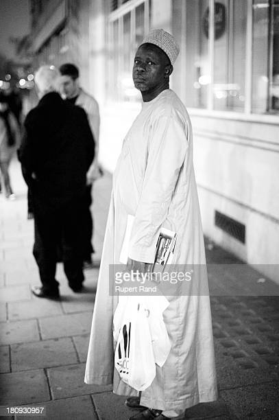 Man of African origin wearing traditional dress waits for a late night bus in London.