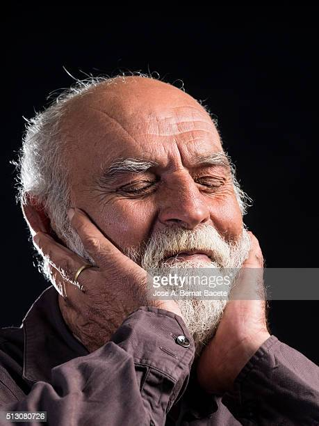 Man of beard and white moustache with gesture of surprise with the hands fighting the face