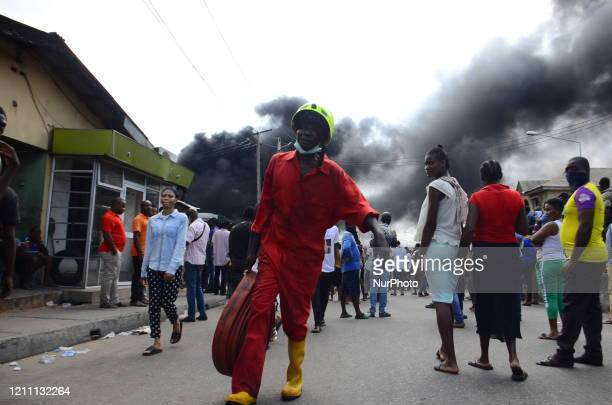 Man of fire fighter walks pass a crowd during the fire outbreak at the Nigerian National Petroleum Corporation petrol station located along College...