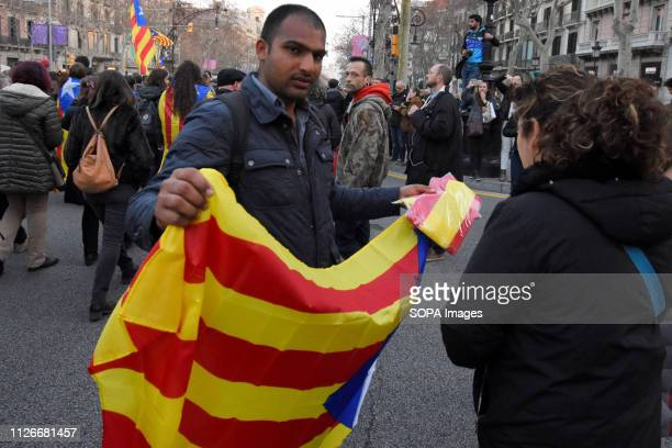 A man of Pakistani nationality sells flags of the independence of Catalonia seen during a general strike in the streets of Barcelona to demand...