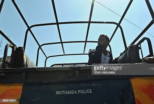 A man of Somali ethinicity hides his face to the photographer while waitint to be transported to a nearby police station after he and others were...