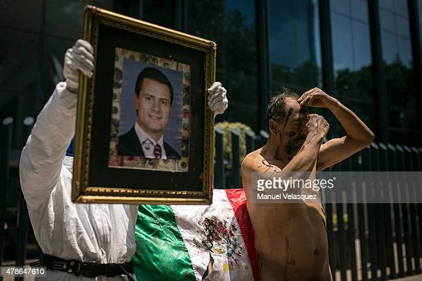 A man of the Arte Accion Cero12 artistic group cuts his face with a razor while another man holds a picture of President Enrique Peña Nieto during...