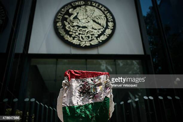 A man of the Arte Accion Cero12 artistic group holds a Mexican flag during the protest as part of the UN's International Day in Support of Victims of...