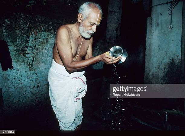 Man of the Brahmin caste pours water into his hand October 28, 1991 in India. Of the five castes in Hinduism, Brahmins occupy the highest level and...