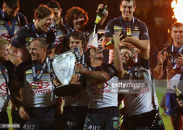 Man of the Match Johnathan Thurston of North Queensland Cowboys drinks champagne as he lifts the World Club Series trophy alongside and Matthew Scott...