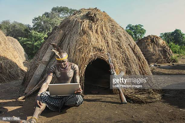 man of the mursi tribe with laptop and kalashnikov gun, omo valley, ethiopia - african tribal face painting stock photos and pictures