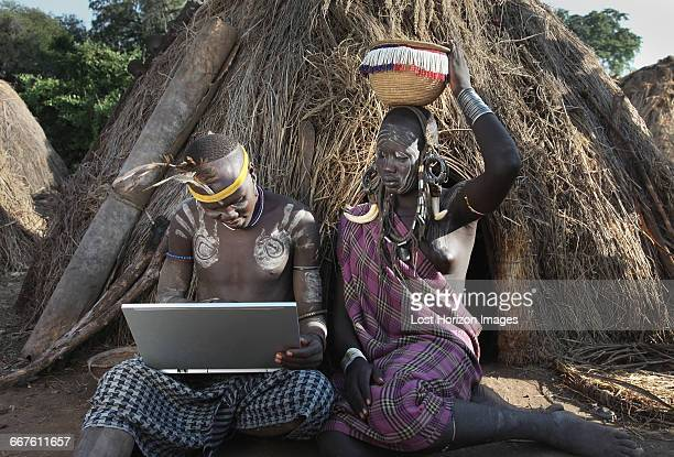 man of the mursi tribe with laptop, sitting beside his wife, omo valley, ethiopia - african tribal face painting stock photos and pictures