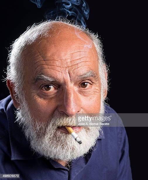 Man of white beard smoking a cigarette