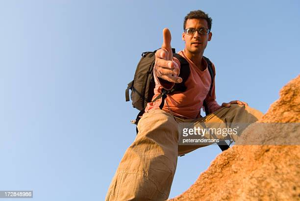 man offering a hand up - cargo pants stock photos and pictures
