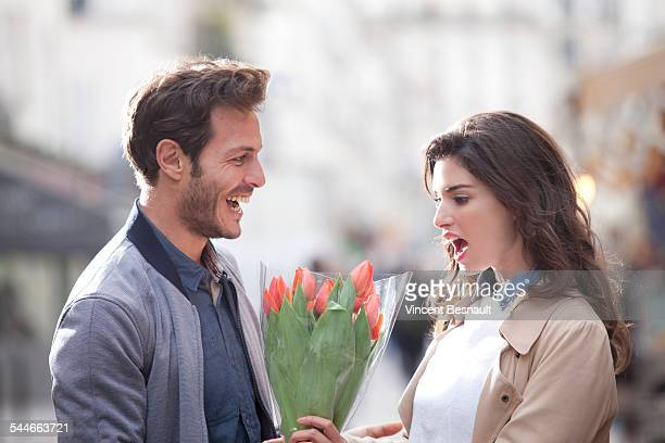 Man offering flowers to a woman in the street