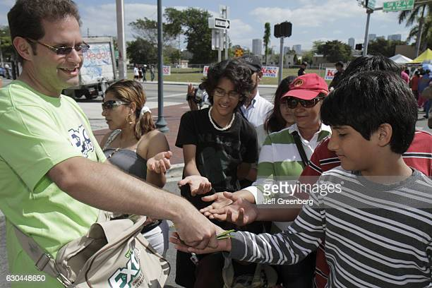 A man offering free samples of Wrigley's gum at the Calle Ocho Street Festival