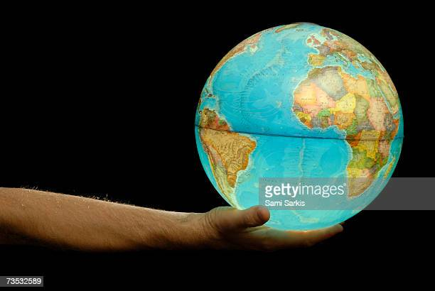 man offering illuminated earth globe, close-up of hand (painterly effect) - world at your fingertips stock pictures, royalty-free photos & images