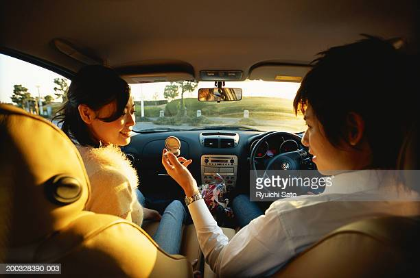 Man offering ring to young woman in car