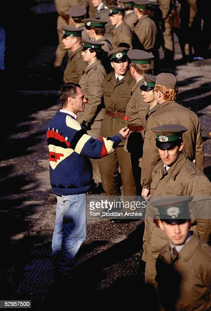 A man offers a flower as a sign of peace to East German border guards on the morning that the first section of the Berlin Wall was pulled down