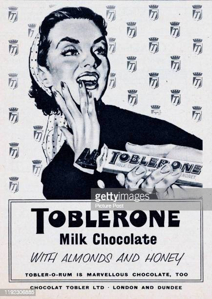 A man offers a woman a piece of a Toblerone chocolate bar Original Publication Picture Post Ad Vol 75 No 5 P 33 pub 4th May 1957