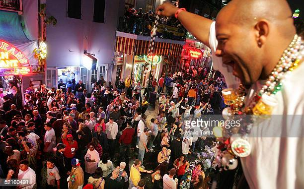 A man offers beads to women crowded on Bourbon Street during Mardi Gras festivities February 8 2005 in New Orleans Louisiana Mardi Gras is the last...