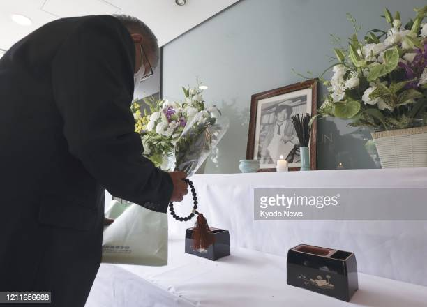 Man offers flowers at an altar set up at a bureau of The Asahi Shimbun newspaper in Nishinomiya, Hyogo Prefecture, western Japan, on May 3 in memory...