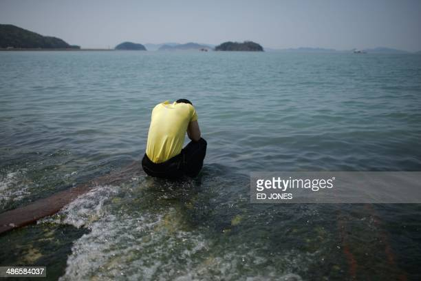 A man offers prayers before the sea for victims of the 'Sewol' ferry at Jindo harbour on April 25 2014 The confirmed death toll from South Korea's...