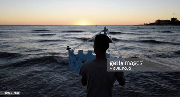 A man offers tribute to Iemanja the Goddess of the Sea of the Umbanda AfroAmerican religion in Montevideo on February 2 2018 Devotees traditionally...