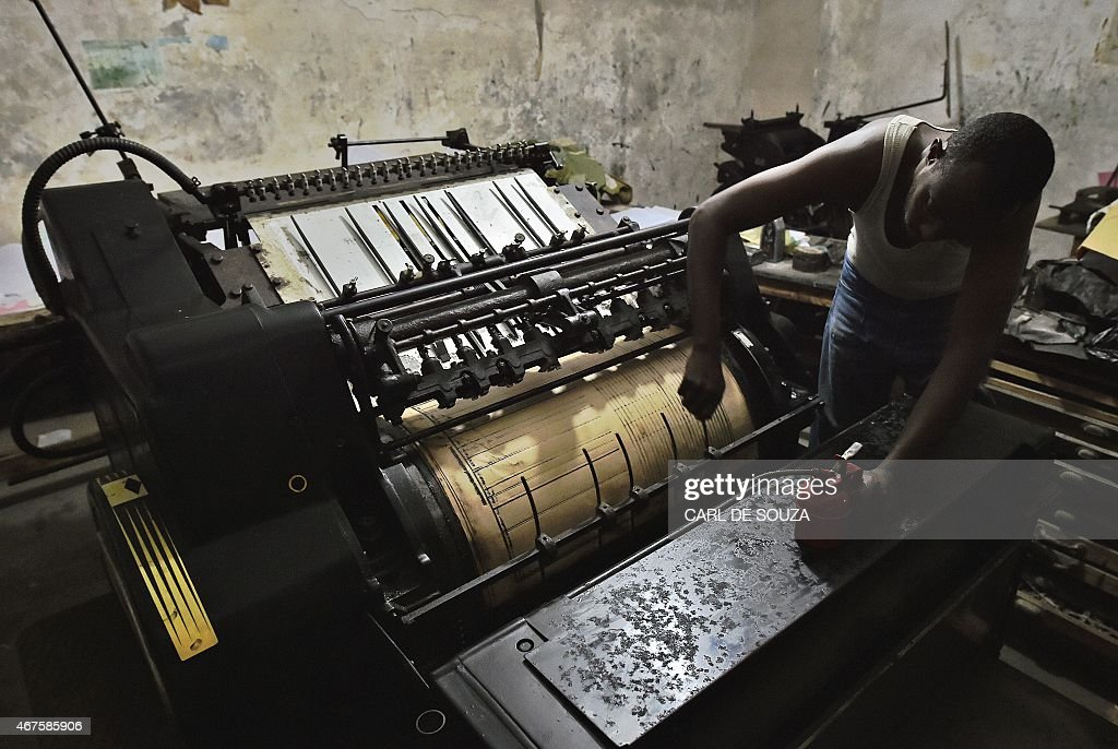 A man oils parts of an old original Heidelberg printing