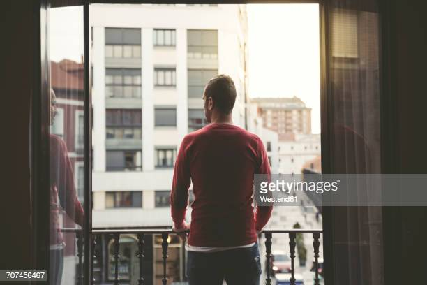 man on a balcony in the city at sunset - balcony stock pictures, royalty-free photos & images