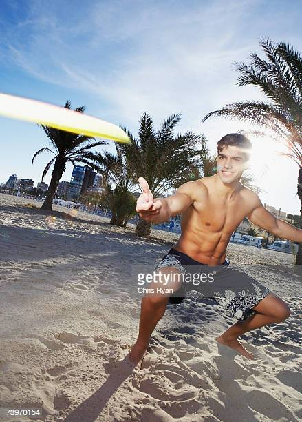 Man on a beach tossing a flying disc toy