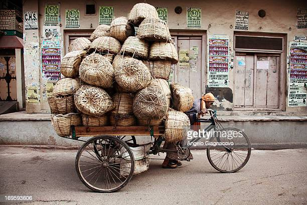 Man on a bicycle carrying baskets of straw.