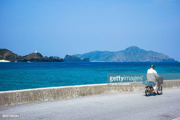 Man on a bicycle in Zamami Island with beautiful beach in Okinawa islands, Ryukyu, Japan