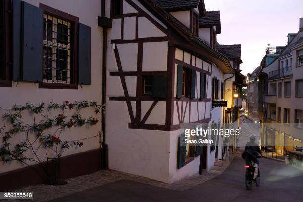 A man on a bicycle rides past 15th and 16th century houses in Rheinsprung street on May 7 2018 in Basel Switzerland Basel a quiet university town on...